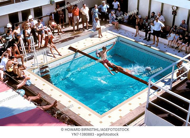 looking down on a couple jousting on the slippery pole across the swimming pool on board an ocean liner