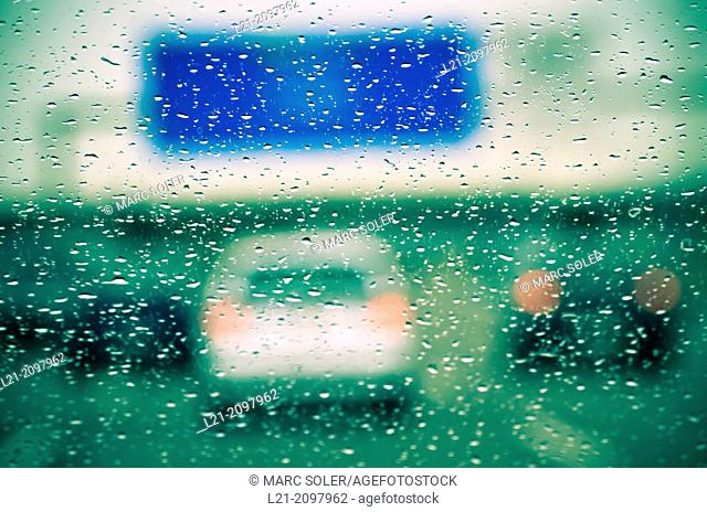 Rain drops on windshield. Blurred view of cars on a highway