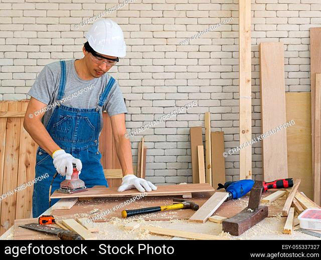Asian carpenter with a hard hat and dustproof glasses use a sander machine to smooth plywood surfaces by abrasion with sandpaper