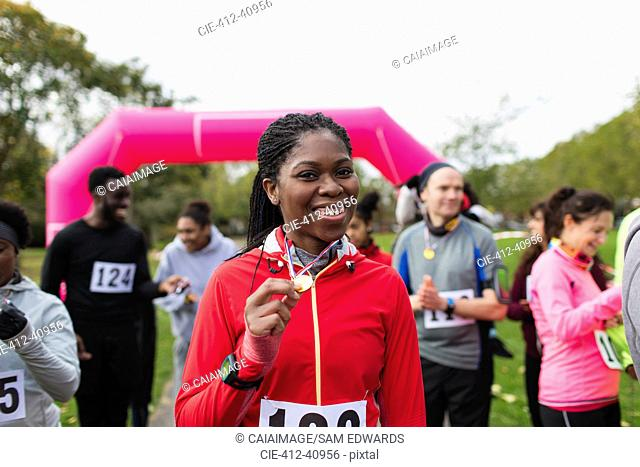 Portrait confident female runner showing medal at charity run