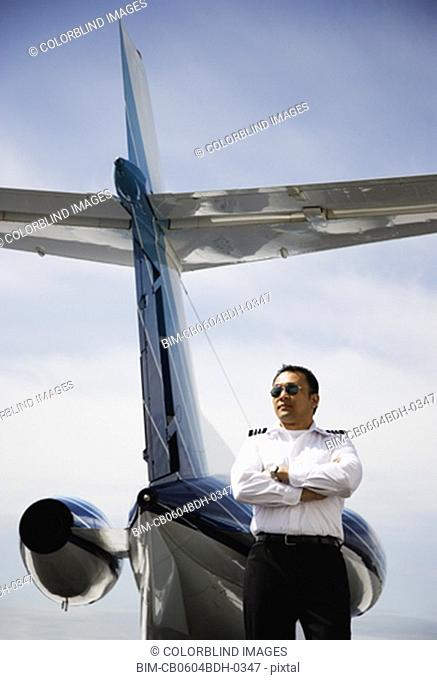 Low angle view of Asian male pilot standing at tail of private airplane