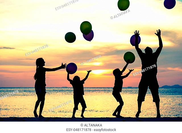 Father and children with balloons playing on the beach at the sunset time. People having fun on the beach. Concept of friendly family and of summer vacation