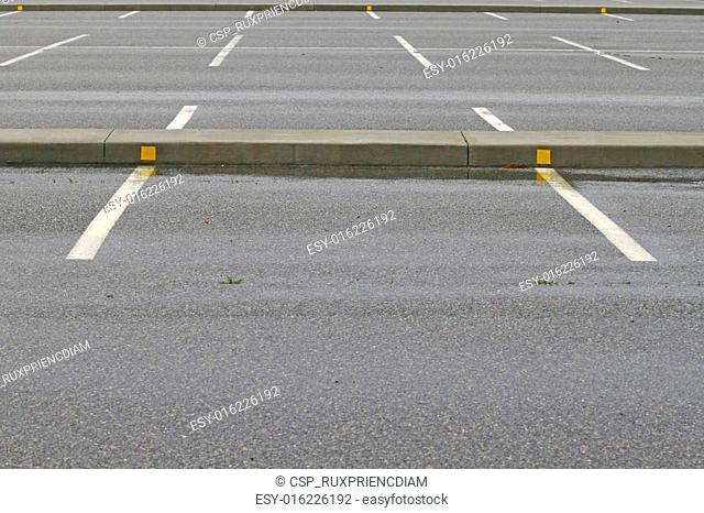 A parking lot full of wet rain covered parking spaces with room for your text