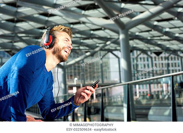 Portrait of a cool guy laughing with headphones