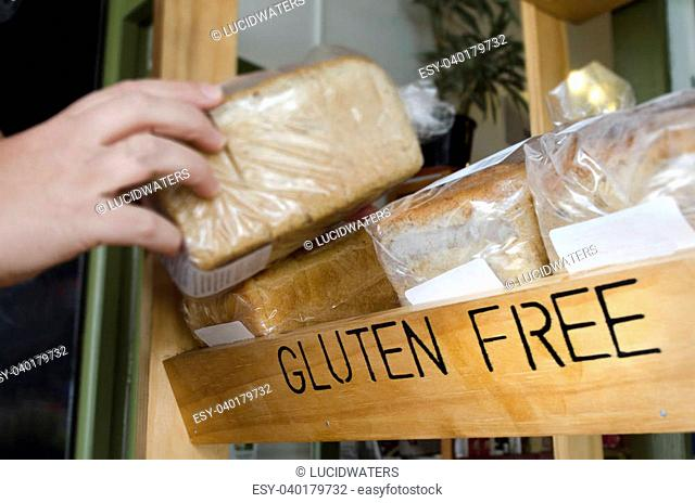 A woman hand picks up a Gluten Free loaf of bread