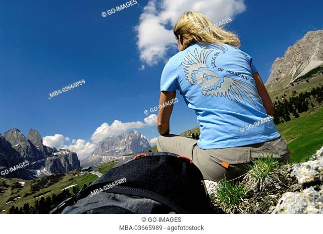 Woman sits in meadow in the dolomites