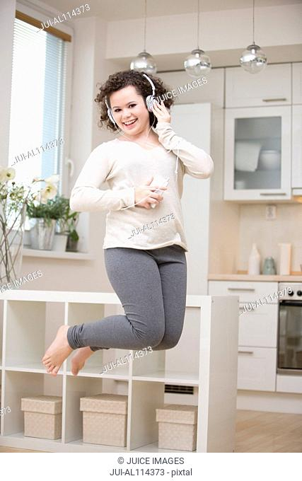 Teenage girl dancing to mp3 player, jumping