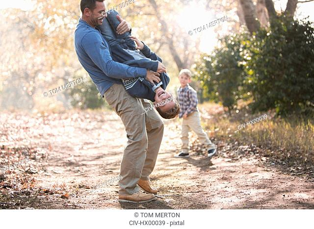 Playful father lifting son upside-down on path in woods
