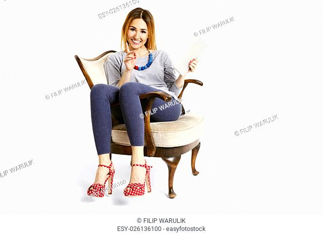 Young woman sitting on a retro chair with tablet explaining and pointing with a finger