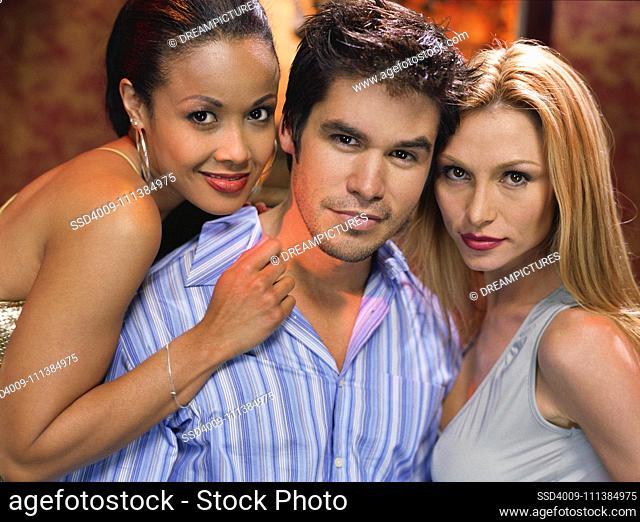 Multi-ethnic women hugging man