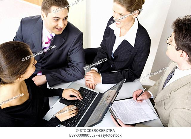 Team of four business people sitting at the table and discussing important questions