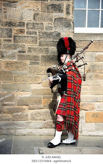 A man playing the bagpipes in full regalia, marching through Edinburgh's Old Town; Edinburgh, Scotland