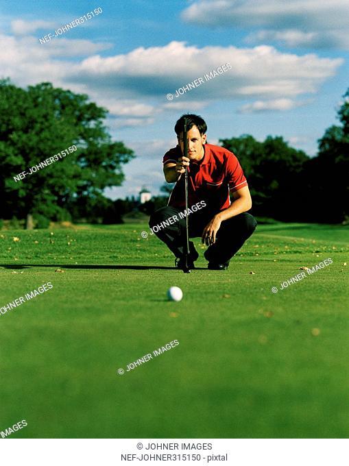 Scandinavian male golfer lining up putt, Sweden