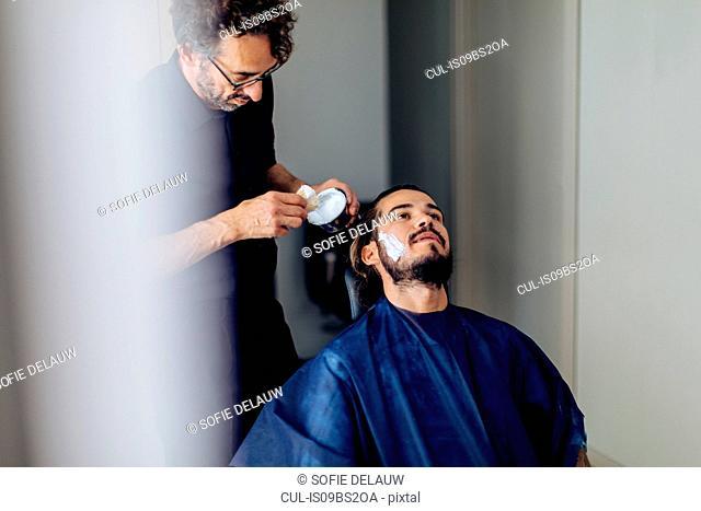 Male hairstylist applying shaving cream at hair salon