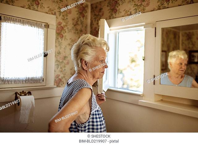 Older Caucasian woman examining herself in mirror