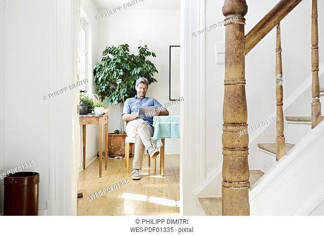 Mature man sitting in his dining room, using tablet