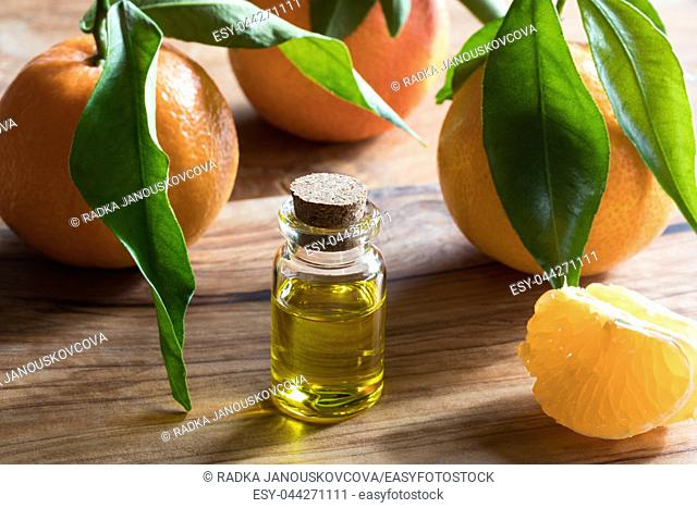 A bottle of tangerine essential oil on a wooden table, with whole tangerines and tangerine wedges in the background
