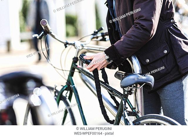 Businessman locking bicycle in the city, partial view
