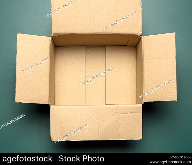 open empty cardboard rectangular box made of corrugated brown paper on a green background, top view