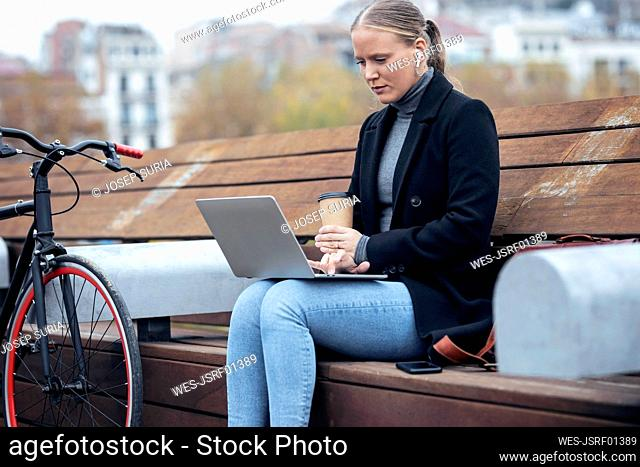 Woman holding coffee cup while using laptop on bench by bicycle