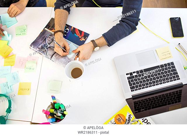 High angle view of business people hands preparing reminders at desk