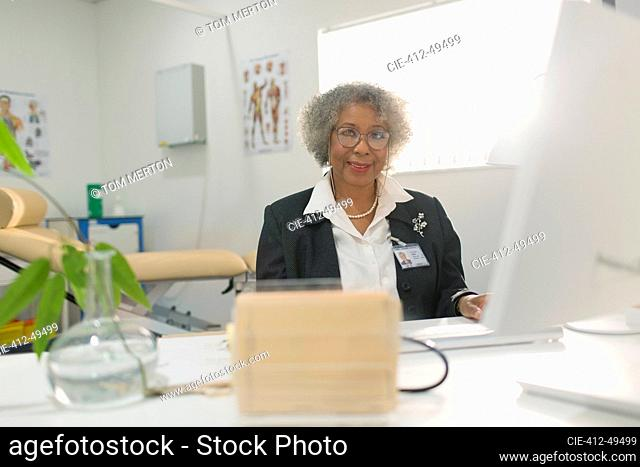 Portrait senior female doctor working at computer in doctors office