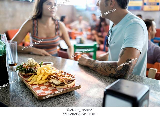 Hamburger and French fries on counter in a bar with couple socializing in background