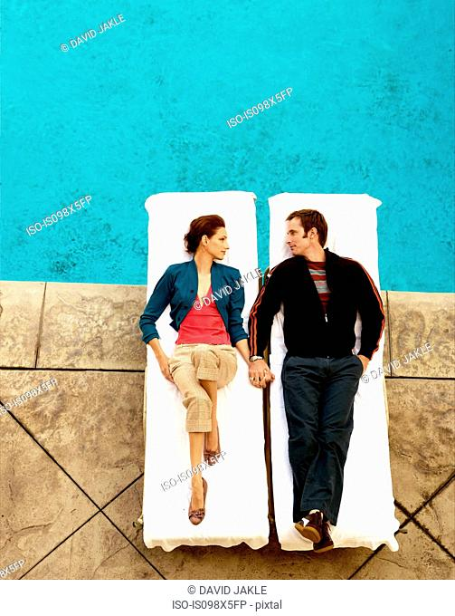Couple lying on lounge chairs at poolside