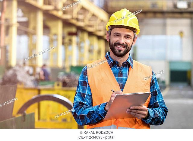 Portrait smiling steel worker with clipboard in factory