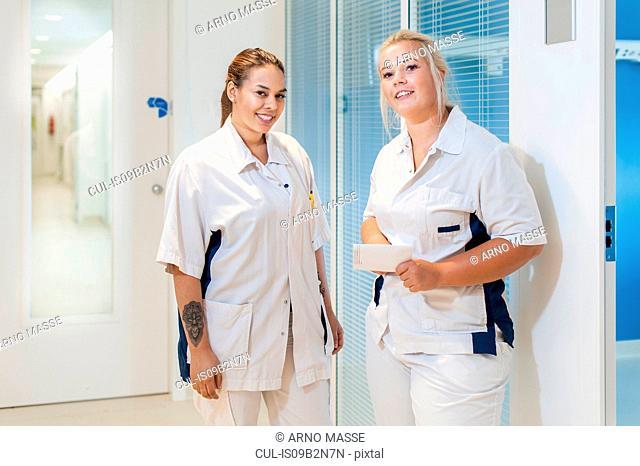 Nurses on hospital ward looking at camera smiling