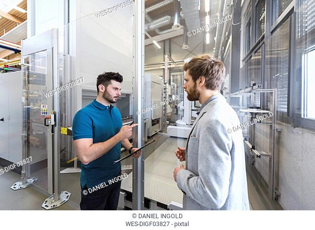 Businessman and employee discussing in modern factory