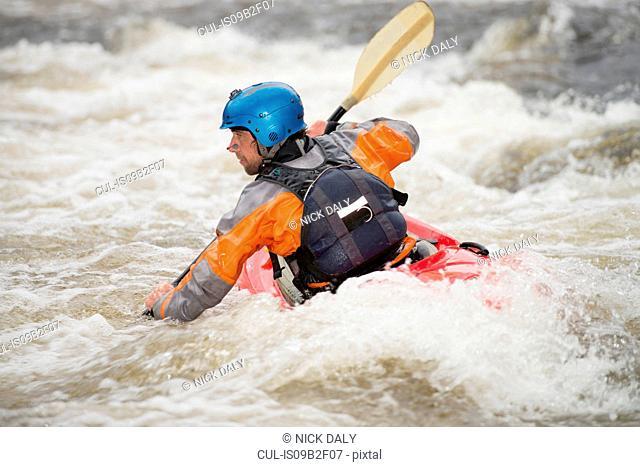 Rear view of male kayaker paddling River Dee rapids