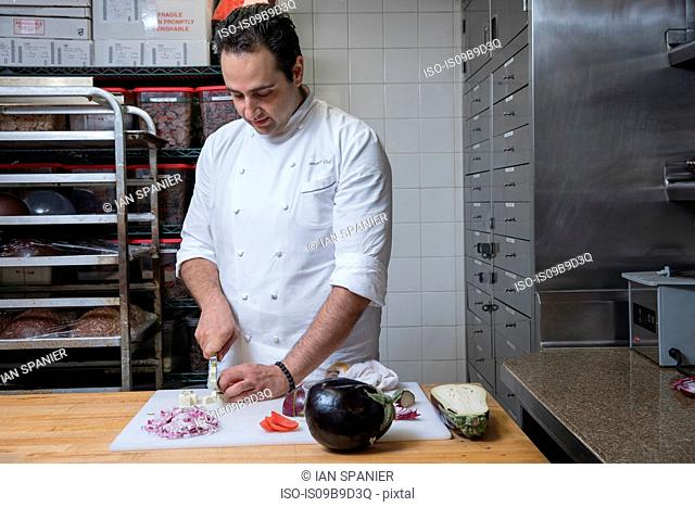 Chef in commercial kitchen slicing aubergine