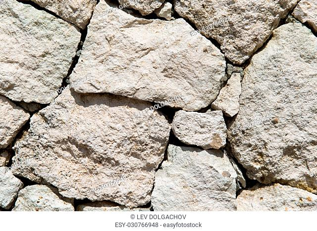 stonework, masonry, background and texture concept - grainy stone wall