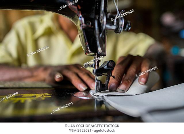 A Salvadoran shoemaker works on a sewing machine, stitching shoe uppers, in a shoe making workshop in San Salvador, El Salvador