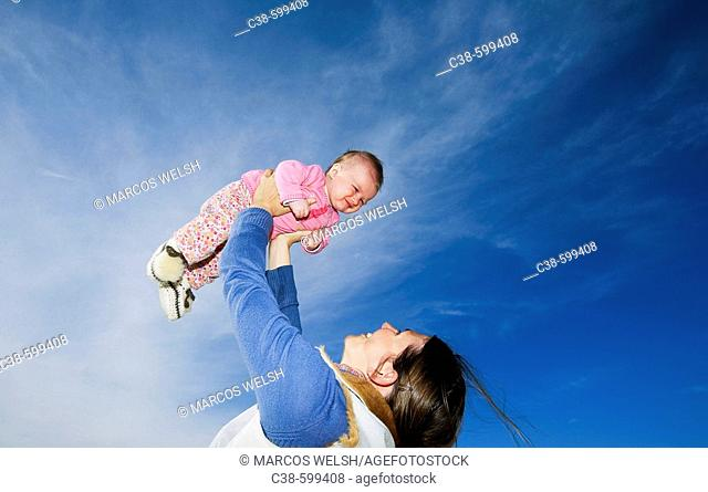 Mother Holding Her Baby Up in the Sky