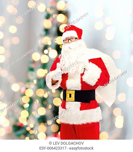 christmas, holidays, gesture and people concept - man in costume of santa claus with bag showing thumbs up over tree lights background