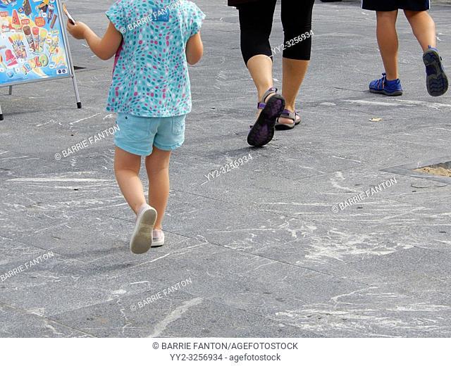 Closeup of Family Walking on Promenade, San Sebastián, Spain