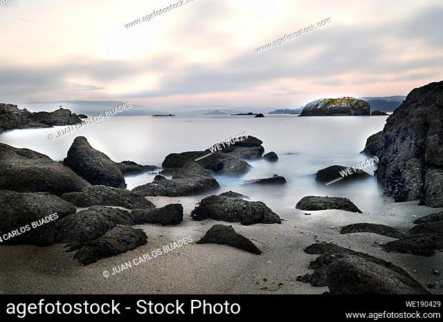 Photograph of long exposure at sunset on unspoilt beach of the coast of vigo in Galicia