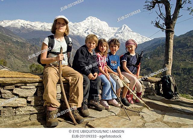 Western children trekking in Himalayan Nepali hills near Pokhara