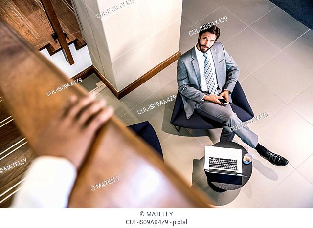 High angle view of businessman in lobby holding smartphone looking up