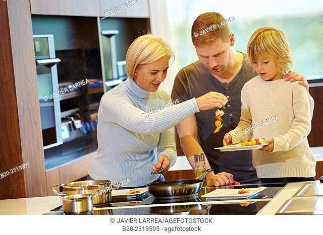 Family in the kitchen. Three generations. Healthy eating. Healthy growth. Cooking fish and vegetable skewer