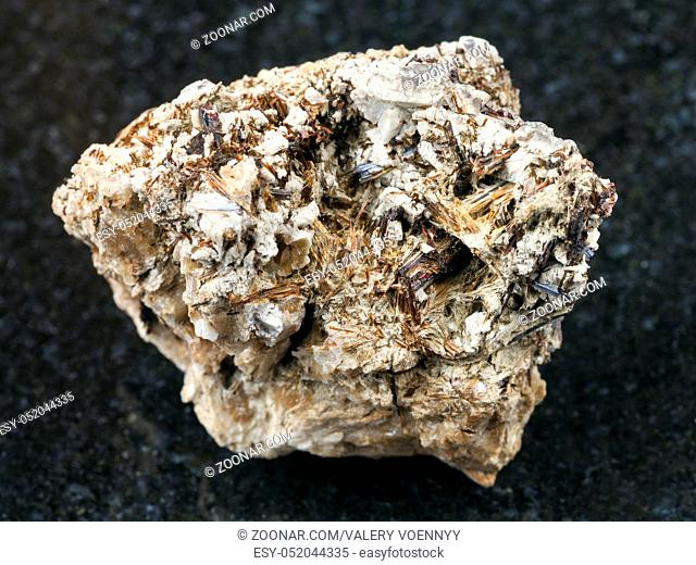 macro shooting of natural mineral rock specimen - brown Astrophyllite crystals in raw Natrolite stone on dark granite background from Khibiny Mountains