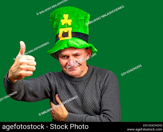 St. Patrick in a green top hat with clover. St.Patrick 's Day. Background image. Place for text. Male model