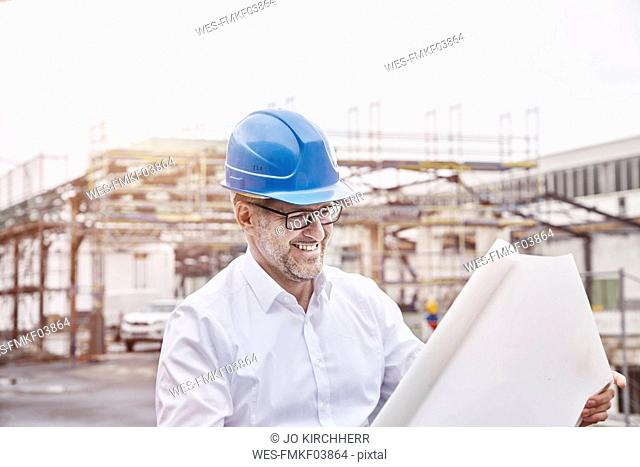 Portrait of laughing man wearing blue hart hat looking at construction plan