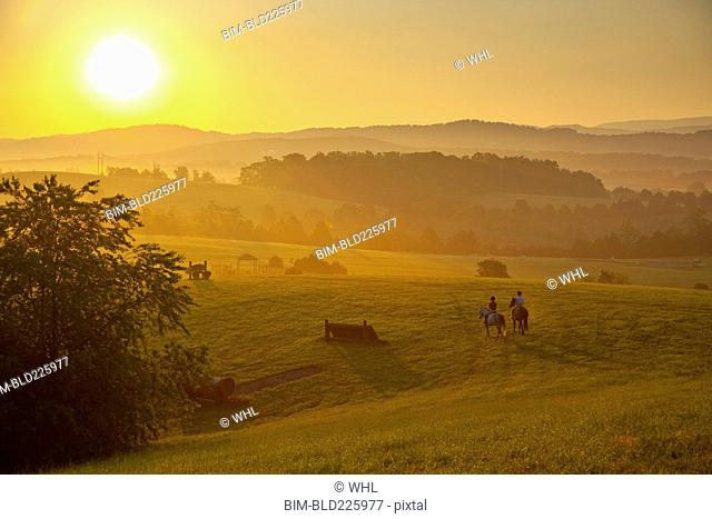 People horseback riding at sunset