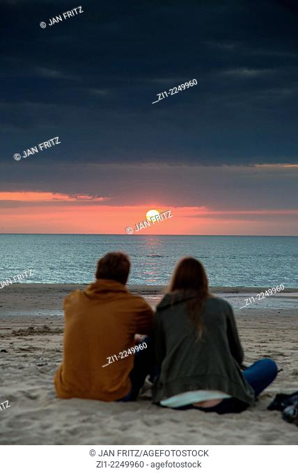 A couple sitting in the sand at the beach enjoying the sunset