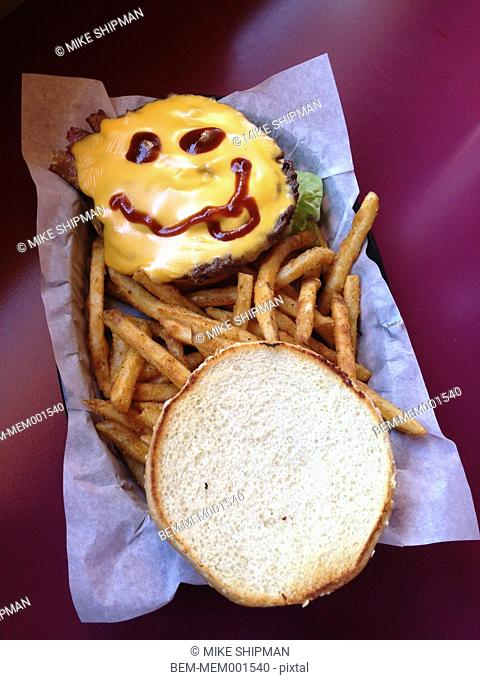 Hamburger with face drawn in ketchup and fries on restaurant table