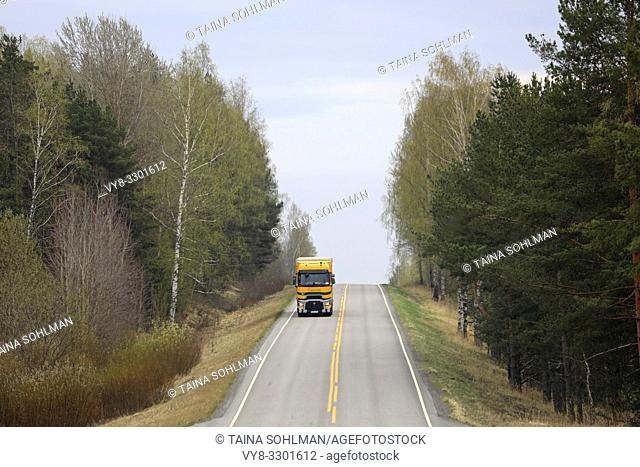 Salo, Finland - April 26, 2019: Road landscape on a day of spring with yellow and green Renault Trucks T semi trailer transporting load