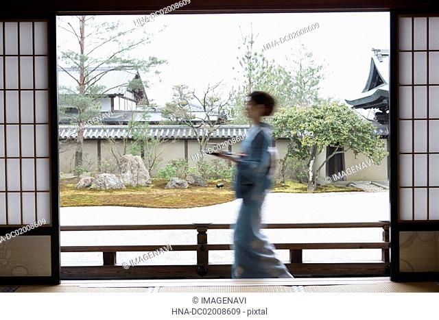 Young Japanese woman in kimono with tray walking on wooden porch